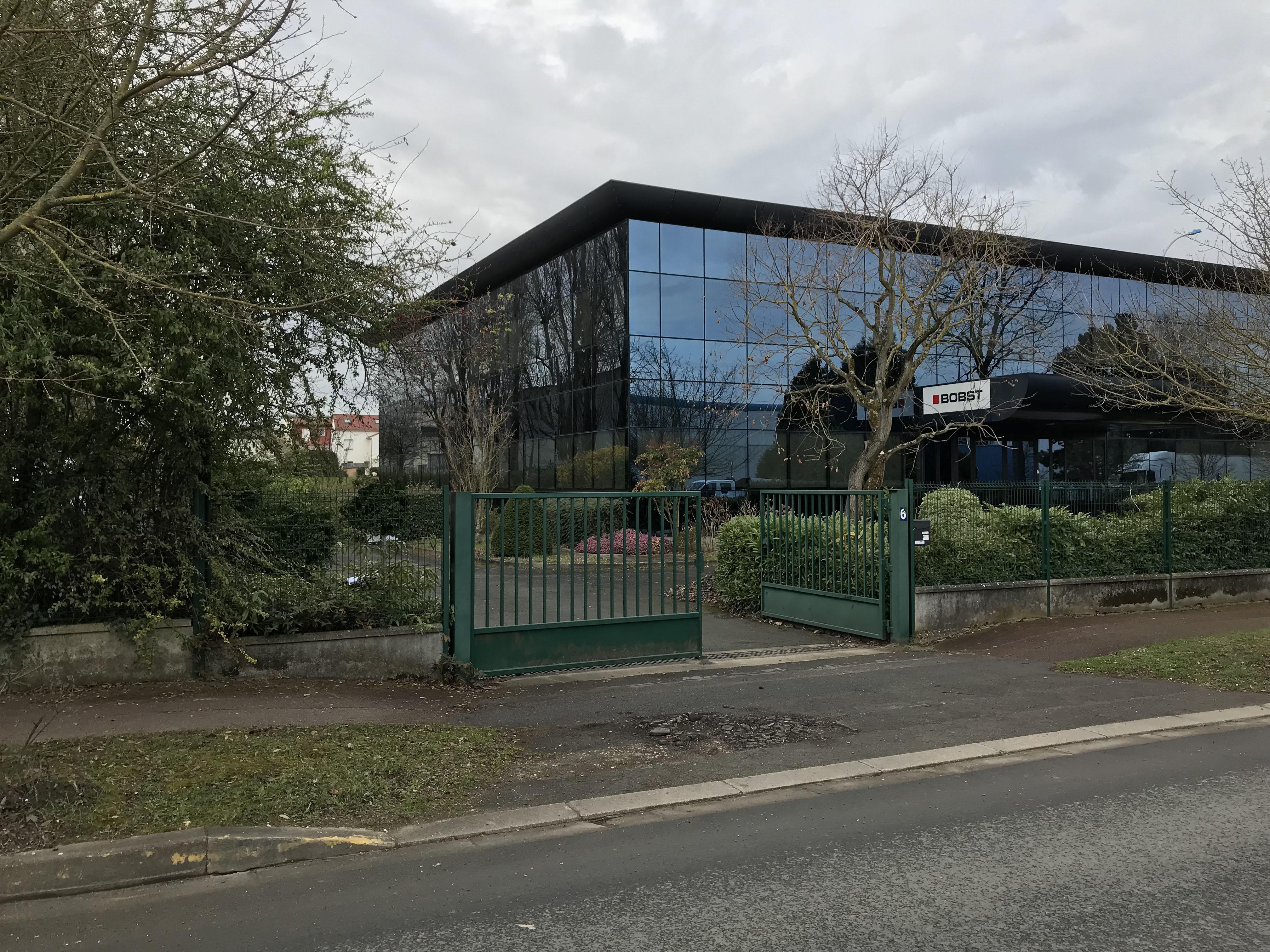 photo du bâtiment et de de l'entrée de l'atelier de mosaïque Mosaïc Concept avec un accès parking à l'arrière